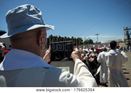 Fatima Portugal - May 13 2014: Priest taking a photograph with his mobile phone at the Sanctuary of Fatima during the celebrations of the apparition of the Virgin Mary in Fatima Portugal.