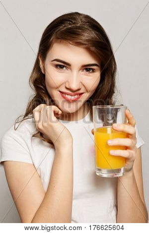 springhealth people youth and beauty concept - head and shoulders portrait of attractive caucasian smiling woman studio shot drinking orange juice face skin. Woman juice glass . Female model hold orange juice glass