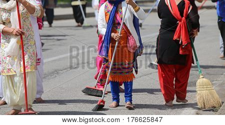 Sikh Women While Scavenging The Street With A Broom During A Fes