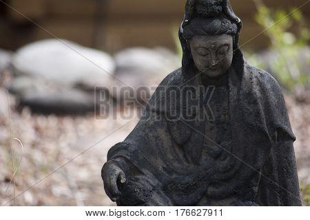 Small stone statue of Buddha in garden.