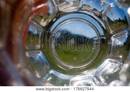 A view looking through an empty drinking glass on a summer day.