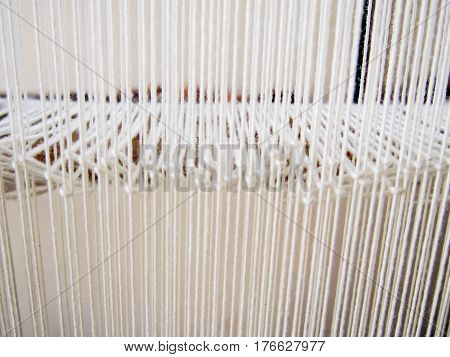 Many strands of white yarn on a loom make a bright pleasant pattern.