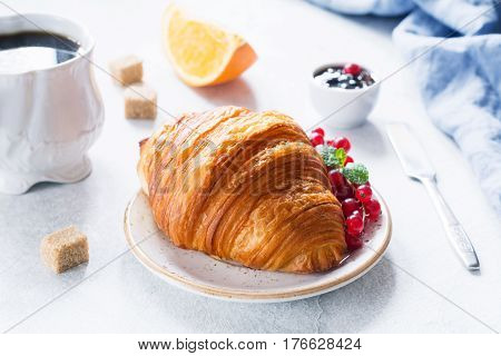 Continental breakfast with croissant, fresh berries, fruit jam and cup of black coffee on white table