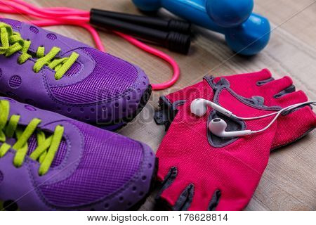 Fitness gym equipment. Sneakers, dumbbells with skipping rope. Workout gloves and footwear. Sport trainers and music headphones.