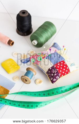 set concept for sewing. production of quilt. measure tape, color bobbin of thread, pin cushion with multicolored sewing pins, buttons and fabric pieces on a white background. tool kit of the tailor.