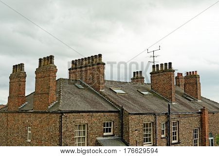 Old Clay Chimney Pots And Brick Chimney Stacks On Old Tiled Roof Complete With Tv Aerials In England