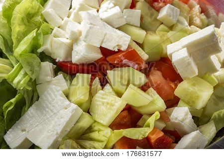 Fresh raw ingredients and romanian white cheese telemea for salad in bowl