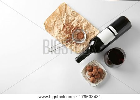 Delicious truffles and red wine on white table