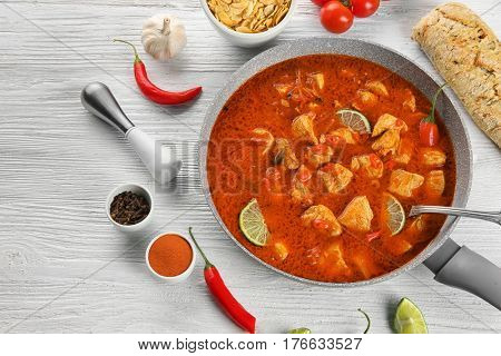 Delicious chicken tikka masala in pan and ingredients on white wooden table