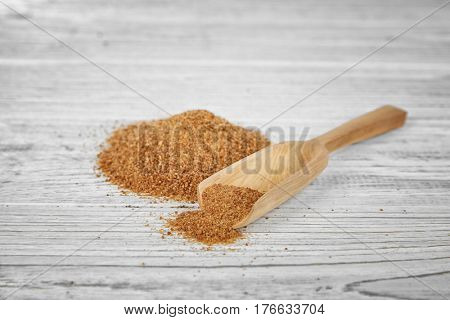 Wooden scoop and heap of coconut sugar on white background