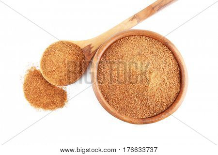 Bowl, wooden spoon and heap of coconut sugar on white background