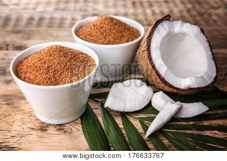 Bowls of coconut sugar on wooden background
