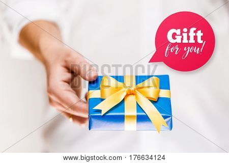 Male hand holding a gift box. Present wrapped with ribbon and bow. Gift for you speech bubble. Man in white shirt.