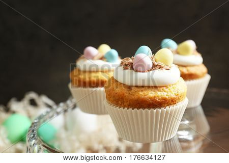 Tasty Easter cupcakes on glass cake-stand against dark background