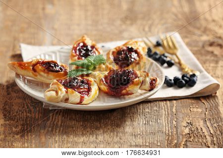Sweet tasty pastries and fresh bilberries on wooden background