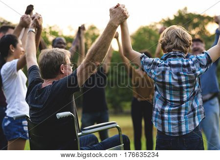 Group of people holding hand together in the park