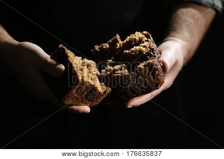 Man breaking off piece of bread on dark background, closeup