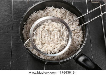 Cooked rice in saucepan with sifter on grate