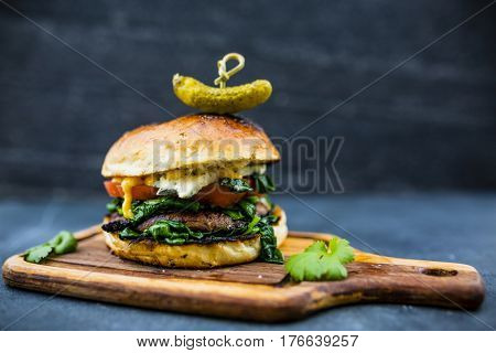 Tasty grilled vegetarian Champignon burger with spinach lettuce and blue cheese served on wooden table with copyspace, blackboard in background.