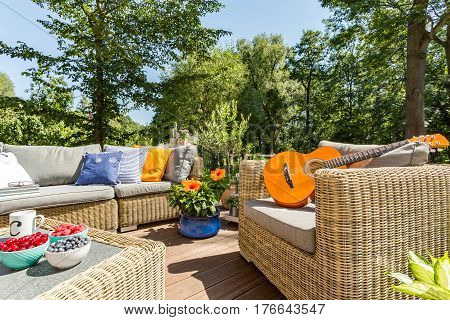 Summer Patio With Rattan Furniture And Guitar