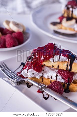 Belgian waffles with raspberries and double cream on white plate.