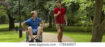 Man Walking With Friend On A Wheelchair