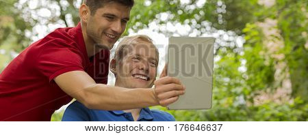 Man Taking Selfie Of Him And Disabled Friend