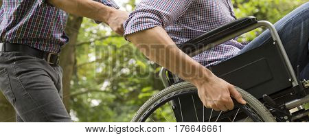 Man Helping His Friend On Wheelchair