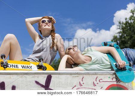 Girls Lying On A Vert Ramp With Skateboards