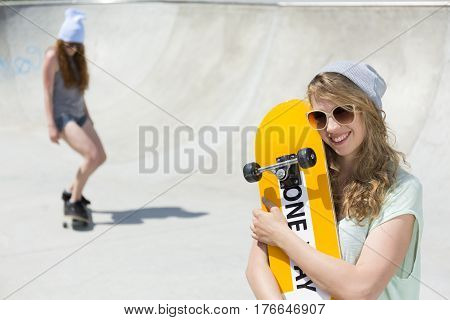 Smiling Young Girl Hugging Her Skateboard