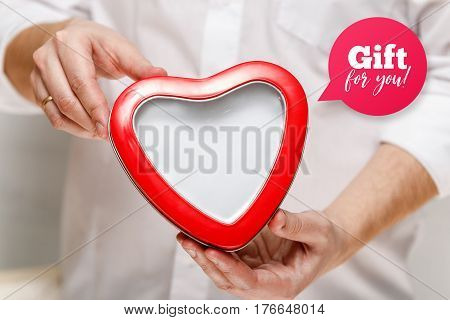 Male hands holding a heart-shaped gift box. Present wrapped with ribbon and bow. Gift for you speech bubble. Man in white shirt.