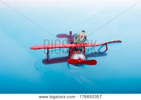 Model Airplane And A Man Figurine In Water