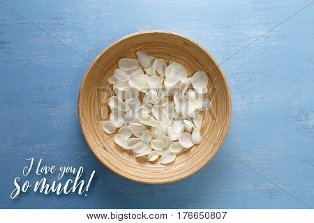 Petals of white roses on blue painted rustic background. Fresh natural flowers in bowl. I love you so much. Dirty grunge wooden board.