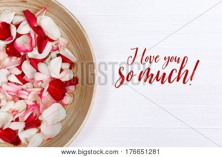 Petals of red, pink roses on white painted rustic background. Fresh natural flowers in bowl. I love you so much.