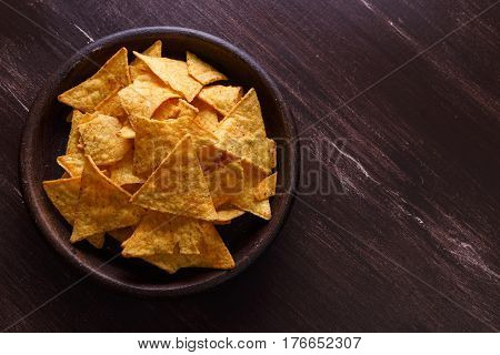 Nachos chips. Delicious salty tortilla snack on rustic plate. On wooden table background.