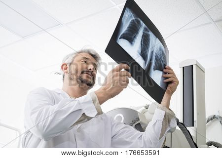 Male Radiologist Analyzing Chest X-ray In Examination Room