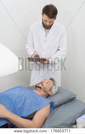 Doctor Writing On Clipboard While Man Undergoing Bone Densitomet