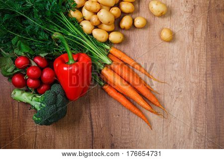 Potatoes with carrot and pepper. Red radish, brocoli and raw new potato. Fresh natural vegetables. Organic bio food. On wooden table.