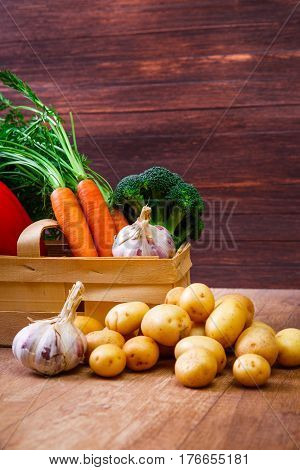Vegetables. Potatoes, carrot and red pepper. Garlic and brocoli. Natural organic bio food. Wooden basket on rustic table.