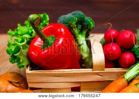 Vegetables. Carrot and red pepper. Lettuce salad and brocoli. Onion and radish. Wooden basket on rustic table.