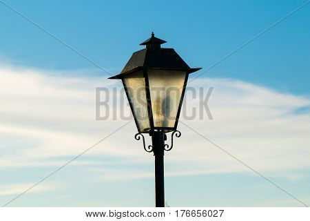 Head of an old fashioned style lamppost against a blue sky