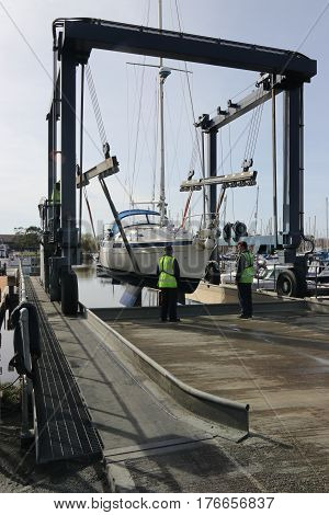 14TH MARCH 2017,CHICHESTER,ENGLAND: A yacht being lowered into the water using a boat cradle sling in chichester marina ,england on the 14th march 2017