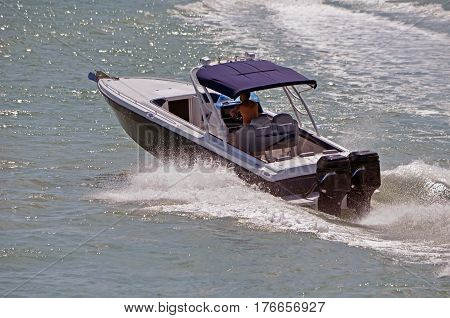 Blaack and white motor boat powered by twin outboard engines speeding on the florida intra-coastal waterway near Miami Beach.