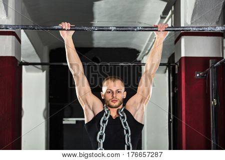 Athlete Man Wearing A Metal Chain Doing Pull-ups On Horizontal Bar In The Gym