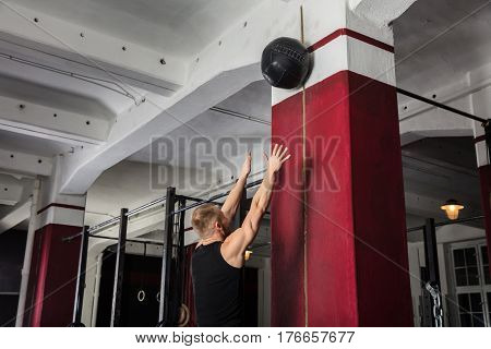 Young Male Athlete Doing Wall Balls Exercise At The Gym