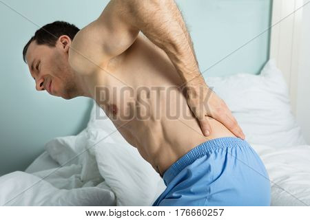 Close-up Of A Man Sitting On Bed Suffering From A Back Pain At Home