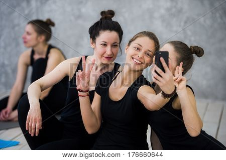 Yoga class of cheerful millennial friends people takes a selfie.