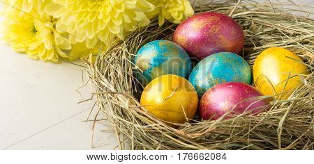 Easter eggs in a straw nest Easter bunny cookies and yellow flowers lie on the background of a white table