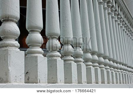 Closeup View of Receding Wooden Fence Posts along a Porch