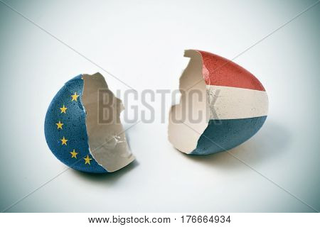 the two halves of a cracked eggshell, one patterned with the flag of the European Community and the other one patterned with the flag of the Netherlands